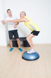 39307340 - coach helps senior with bosu exercise