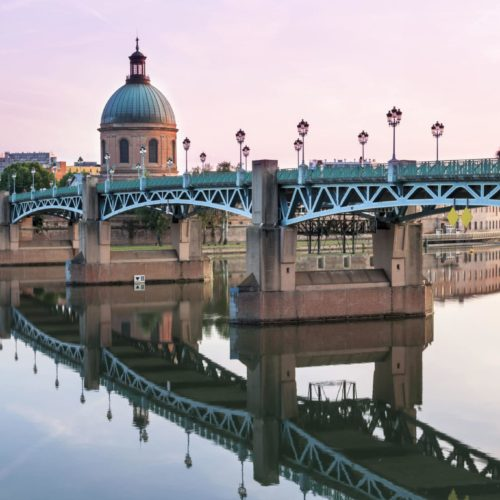 Saint-Pierre Bridge reflecting in Garonne river and Dome de la Grave at sunset in Toulouse, France